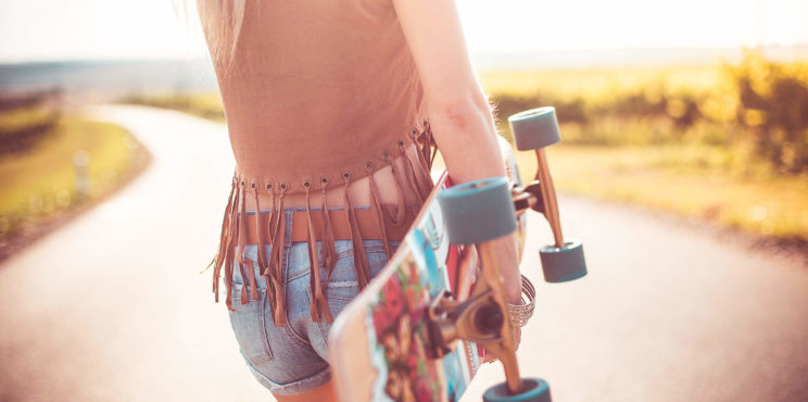 Young Woman Walking on The Road and Holding Longboard
